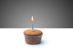 Delicious festive muffin with a candle standing on the table.  Stock Images