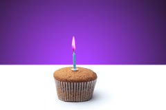 Delicious festive muffin with a candle standing on the table.  Royalty Free Stock Image