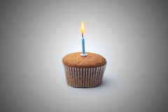 Delicious festive muffin with a candle standing on the table.  Stock Photography