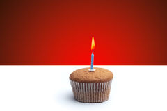 Delicious festive muffin with a candle standing on the table.  Royalty Free Stock Photography