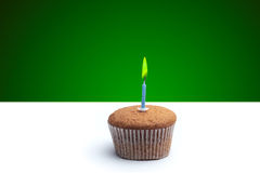 Delicious festive muffin with a candle standing on the table.  Stock Photos