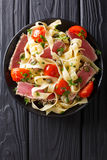 Delicious fettuccine pasta with tuna steak, tomatoes and capers. Close-up on a plate on a table. Top view from above vertical Royalty Free Stock Images