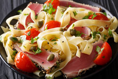 Delicious fettuccine pasta with tuna steak, tomatoes and capers. Close-up on a plate on a table. horizontal Royalty Free Stock Photo