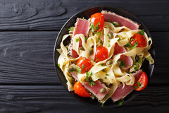 Delicious fettuccine pasta with tuna steak, tomatoes and capers. Close-up on a plate on a table. Top view from above horizontal stock image
