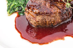 Delicious fillet mignon steak with chard. Delicious grilled fillet mignon steak with chard covered with red wine sauce. Macro. Selective focus on the steak royalty free stock images