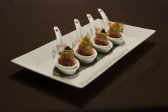 Delicious finger fusion food in white spoons. On black table royalty free stock photo