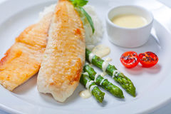 Delicious fish steak with green asparagus and rice Stock Image