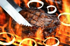 Delicious flame broiled rib eye steak on a flaming grill. A delicious rib eye steak on a hot flaming grill with onions royalty free stock photography