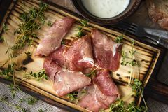 Delicious flavorful ham sliced ​​into strips on a wooden background with spices and fresh thyme. A serving of low-fat. Succulent farm meat pork stock photos