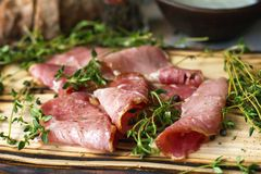 Delicious flavorful ham sliced ​​into strips on a wooden background with spices and fresh thyme. A serving of low-fat. Succulent farm meat pork royalty free stock photography