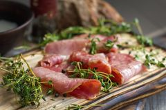 Delicious flavorful ham sliced ​​into strips on a wooden background with spices and fresh thyme. A serving of low-fat. Succulent farm meat pork stock photo