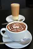 Delicious foamy cappuccino on a white cup on a plate. Royalty Free Stock Images