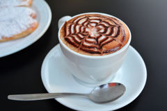 Delicious foamy cappuccino on a white cup on a plate. Royalty Free Stock Photo