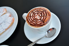 Delicious foamy cappuccino on a white cup on a plate. Stock Photos
