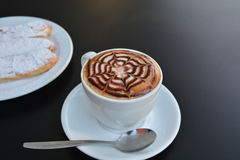 Delicious foamy cappuccino on a white cup on a plate. Royalty Free Stock Photos