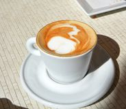 Delicious foamy cappuccino on a white cup on a plate. Stock Image