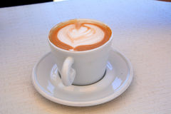 Delicious foamy cappuccino on a white cup on a plate. Stock Images