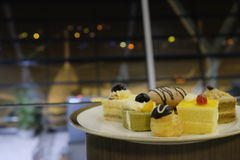 Delicious cake and bread in airport with plane behind. In airport, several cake and bread been put in one dish. An airplane behind Royalty Free Stock Images