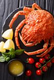 Delicious food: boiled spider crab with tomato, lemon and melted. Butter close-up on a black board. Vertical top view from above stock image