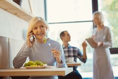 Cheerful elderly woman eating her salad. Delicious food. Cheerful positive elderly women smiling and eating her salad while talking on the phone Royalty Free Stock Photos