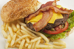 A delicious cheese burger with bacon and french fries Royalty Free Stock Photography