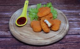 Chicken nuggets. Delicious food , chicken nuggets with cheese and sauce on a wooden board Stock Images