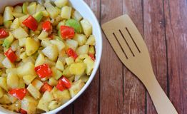 Delicious food ,fried potatoes with vegetables. On a wooden background Stock Photos