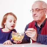 Delicious food. Grandpa feeding his grandchild with fruits salad Royalty Free Stock Photo