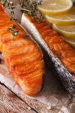 Delicious food: grilled salmon with lemon on the paper macro. ve Stock Photos