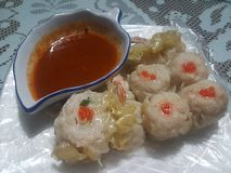 Delicious food from hongkong: Dim Sum. Dim Sum chicken flavor with Red Chili on a white table background stock image