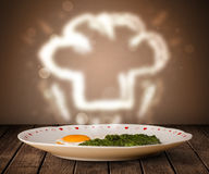 Delicious food plate with chef cook hat Stock Photography