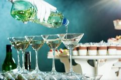 Delicious food on the wooden table. Cropped close up of a waiter wearing white glove pouting martini into the glass on the table at the local restaurant festive stock images