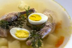 Delicious fragrant soup based on quail broth in a white dining plate. Slices of meat, quail egg, dill, bulgur, pepper and crackers stock images
