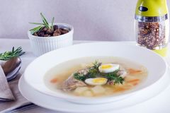 Delicious fragrant soup based on quail broth in a white dining plate. Slices of meat, quail egg, dill, bulgur, pepper and crackers royalty free stock photography