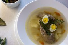 Delicious fragrant soup based on quail broth in a white dining plate. Slices of meat, quail egg, dill, bulgur, pepper and crackers royalty free stock image