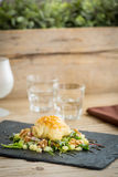 Delicious french cake filled with goat cheese on salad. Stock Images