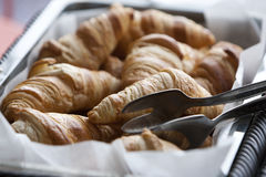 Delicious french croissants. Delicious fresh croissants and silver tong standing beside Stock Photography