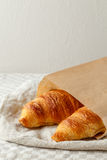 Delicious french freshly baked croissants in paper bag on a textile background. Royalty Free Stock Photo