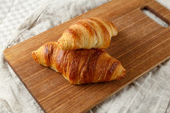 Delicious french freshly baked croissants on a wooden cutting board. Stock Photo