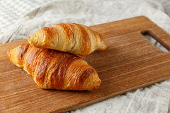 Delicious french freshly baked croissants on a wooden cutting board. Royalty Free Stock Image