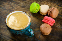 Delicious French macarons almond cookies served. Delicious colourful French macarons almond cookies served with a cup of black coffee Royalty Free Stock Images