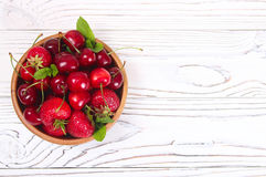 Delicious fresh berries of cherries and strawberries. On a wooden background Royalty Free Stock Images