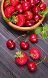 Delicious fresh berries of cherries and strawberries. On a wooden background Royalty Free Stock Photo