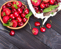 Delicious fresh berries of cherries and strawberries. On a wooden background Royalty Free Stock Image
