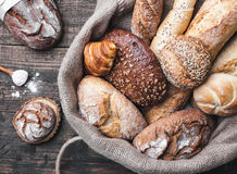 Delicious fresh bread inside a sack on wooden background Royalty Free Stock Photo