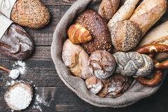 Delicious fresh bread inside a sack on wooden background Stock Images