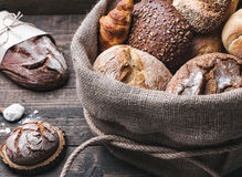 Delicious fresh bread inside a sack on wooden background Stock Photo