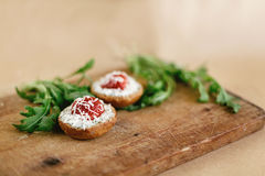 Delicious fresh canape with gorgonzola parmezan and strawberry a. Nd arugula on wooden desk on craft background Royalty Free Stock Photo