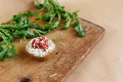 Delicious fresh canape with gorgonzola parmezan and strawberry a. Nd arugula on wooden desk on craft background Stock Photography