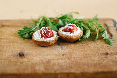 Delicious fresh canape with gorgonzola parmezan and strawberry a. Nd arugula on wooden desk on craft background Royalty Free Stock Photography